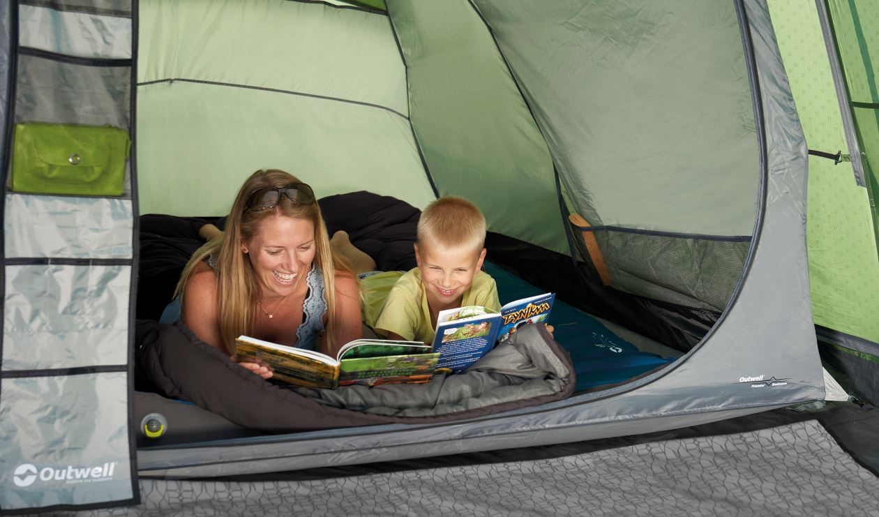 Mum and son reading books in tent on selfinflating mat