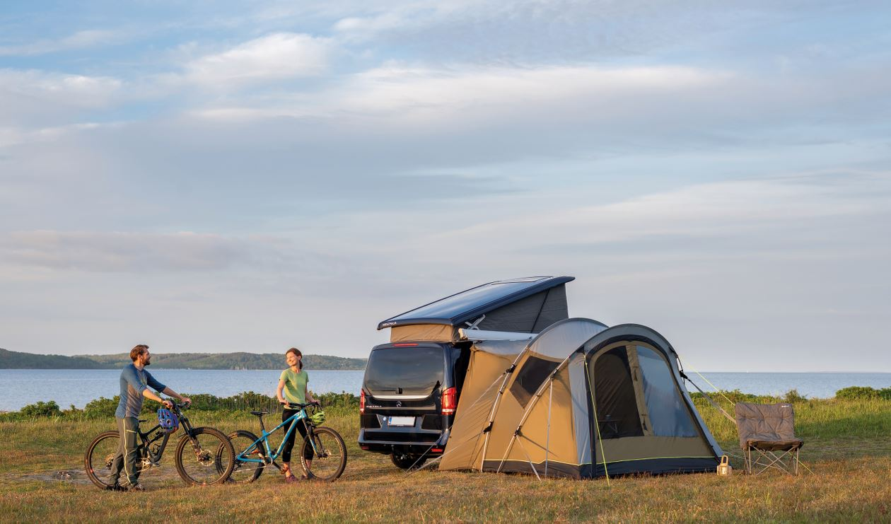 Couple camping with drive-away awning